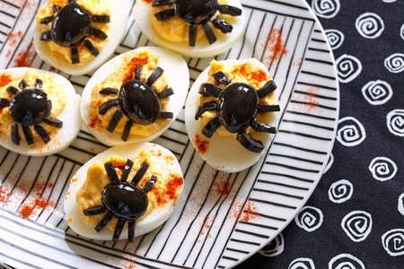 For a family Halloween party, think creative, themed food, such as these spider-like deviled eggs.